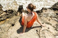Girl in dress on the shore of the Mediterranean Sea. Girl in a red dress on the shore of the Mediterranean Sea Royalty Free Stock Photography
