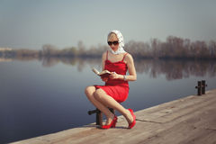 Girl in red dress sitting on a jetty. Blond girl in red dress sitting on a jetty and reading a book Royalty Free Stock Photography