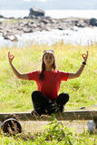 Girl in a red dress sitting in the lotus position Stock Images