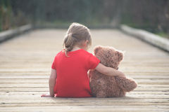 Girl in red dress sitting with teddybear on boardwalk Stock Images