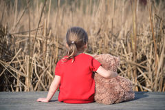 Girl in red dress sitting on a wooden board with teddybear looking at field of yellow grass Stock Photo