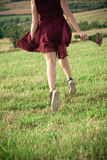 Girl in red dress and sneakers run on summer field Royalty Free Stock Photos