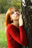 Girl in red dress snuggle up to tree Stock Images
