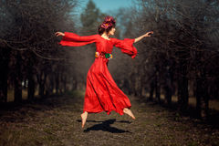 Girl in red dress soars. In autumn park floating girl in a red dress with a wreath on his head like a fairy tale Royalty Free Stock Images