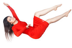 The girl in the red dress soars. The girl in the red dress floating in the air his arms and legs, it is isolated on white background Stock Photos