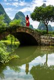 Girl in red dress stand in the old stone bridge. In Yangshuo stock images