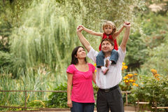 Girl in red dress together with parents in summer Stock Image