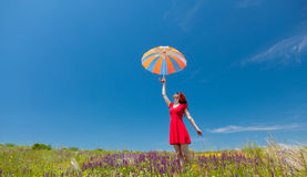 Girl in red dress with umbrella on meadow Royalty Free Stock Photography