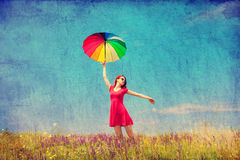 Girl in red dress with umbrella on meadow Stock Photo