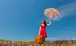 Girl in red dress with umbrella and suitcase Royalty Free Stock Photos