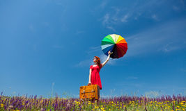 Girl in red dress with umbrella and suitcase Stock Photography