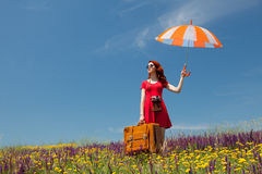 Girl in red dress with umbrella and suitcase Stock Photos
