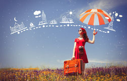 Girl in red dress with umbrella and suitcase Stock Photo