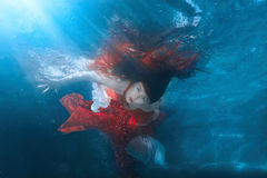 Girl in red dress under water. Royalty Free Stock Photo