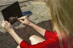 Girl in red dress uses a tablet. On the street. view from above. young woman in a red dress resting in the park with a tablet in her hand. using advanced mobile Royalty Free Stock Images