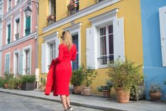 Girl in red dress walk on street of paris, france. Woman with blond hair, back view, on urban environment. Fashion, autumn style concept. Vacation, lifestyle Stock Photography