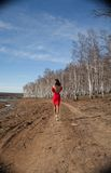Girl in red dress walking Stock Images