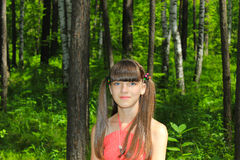 Girl in red dress walks in the woods Stock Photography
