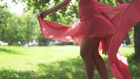Girl in a red dress whirls barefoot on the grass. female legs closeup