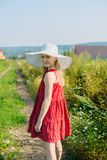 Girl in red dress and white hat with large brim. Going on road in field royalty free stock photo