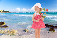 Girl in red dress. And white panama hat on sea background.floral bouquet, flowers delight,happiness concept,happy childhood,carefree childhood,active lifestyle Stock Image