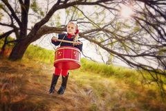 Girl with red drum. Little girl at edge of golden field under tree holding drum sticks and  big red drum Royalty Free Stock Images