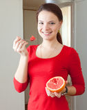 Girl in red eats grapefruit Royalty Free Stock Photo