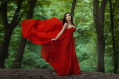 Girl in red on the edge of a precipice. Stock Photos