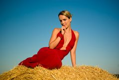 Girl in red evening dress leaning on straw bale. Royalty Free Stock Images
