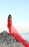 The girl in a red fabric on stones near the sea Stock Photography