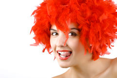 Girl in red feathers with tongue ring exposed Stock Images