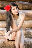 A girl with a red flower in her hair and a white dress sits on logs royalty free stock photo