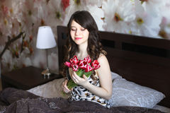 Girl with red flowers in the bed Stock Image