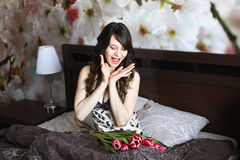 Girl with red flowers in the bed Stock Photos