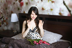 Girl with red flowers in the bed Royalty Free Stock Photography