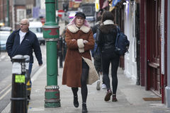 Girl in a red fur coat and cap walking along Brick Lane Stock Images