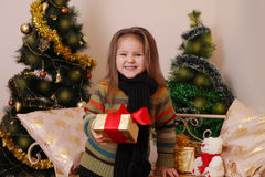 Girl with red giftbox over golden Christmas tree Royalty Free Stock Image