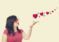 Girl in red glasses and abstract hearts at white background. Stock Photography