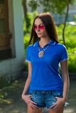 Girl in red glasses and blue shirt Royalty Free Stock Image
