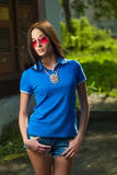 Girl in red glasses and blue shirt Stock Photo