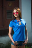 Girl in red glasses and blue shirt Stock Images