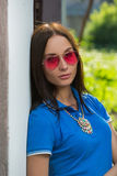 Girl in red glasses and blue shirt Stock Image