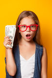 Girl in red glasses with money. Beautiful young girl in red glasses with money on yellow background Stock Photography