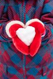 A girl in red gloves holds a heart shaped snowball. Symbol of love. For Valentine`s Day stock images