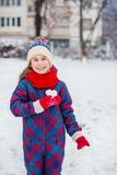 A girl in red gloves holds a heart shaped snowball. Symbol of love. For Valentine`s Day royalty free stock images