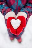 A girl in red gloves holds a heart shaped snowball. Symbol of love. For Valentine`s Day stock image