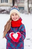 A girl in red gloves holds a heart shaped snowball. Symbol of love. For Valentine`s Day stock photos