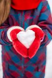 A girl in red gloves holds a heart shaped snowball. Symbol of love. For Valentine`s Day stock photo