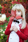 Girl with red grape leaves in arms. In autumn park Royalty Free Stock Image