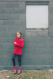 Girl in red on grey wall Stock Images